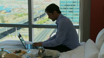 stock-footage-long-shot-pan-of-a-businessman-working-in-his-hotel-room