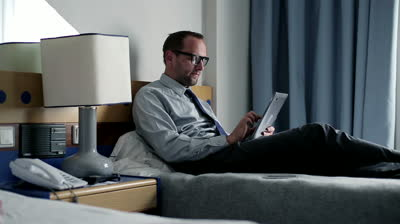 stock-footage-young-businessman-with-tablet-computer-in-hotel-room